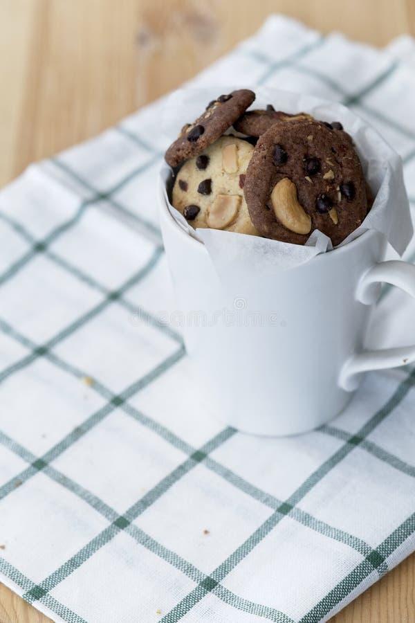 在方格的桌布的可口巧克力曲奇饼,在一个白色杯子的鲜美自创曲奇饼在木桌上 免版税库存照片