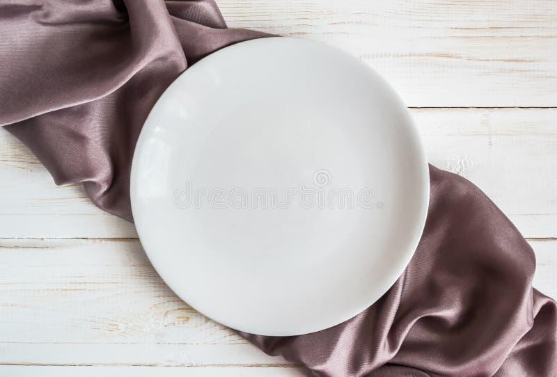 在方格的淡紫色缎餐巾的白色板材 免版税图库摄影