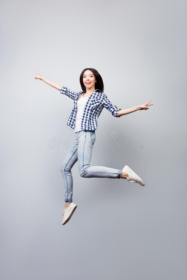 在方格的衬衣和牛仔裤打扮的美丽的快乐的女孩是ju 免版税图库摄影