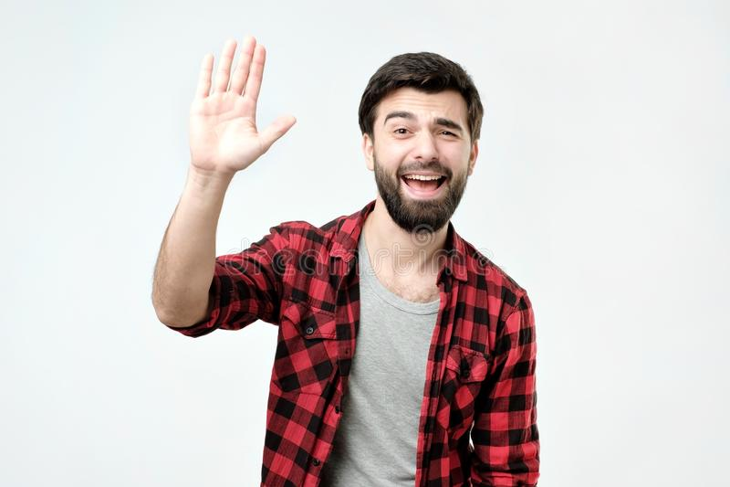 在方格的衬衣打扮的友好的看起来的礼貌的年轻西班牙人说喂 免版税库存图片