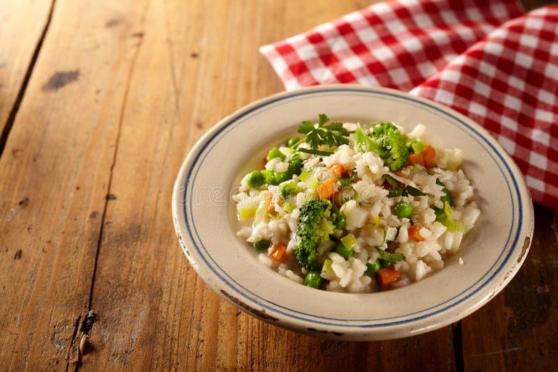 在方格的餐巾旁边的碗意大利煨饭risi bisi和素食者 免版税库存图片