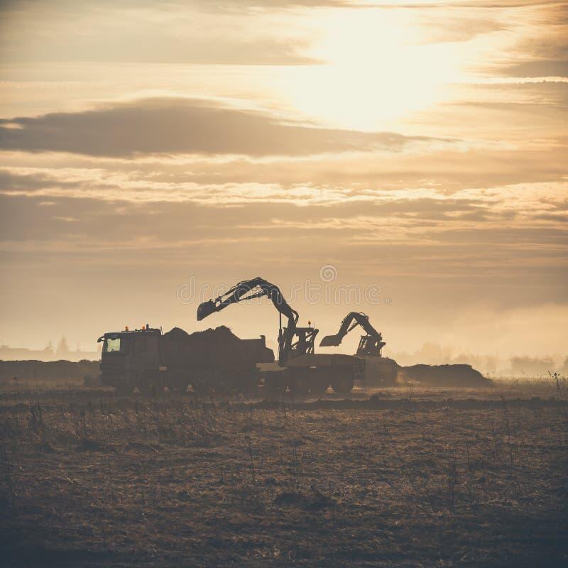 在施工现场、装载自卸车轨道工作的挖掘机 库存照片
