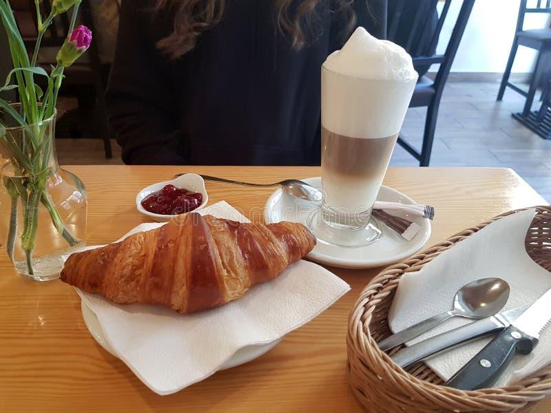 在旁边新月形面包和一份新鲜的咖啡与花和碗筷在一张典雅的桌上 免版税库存图片