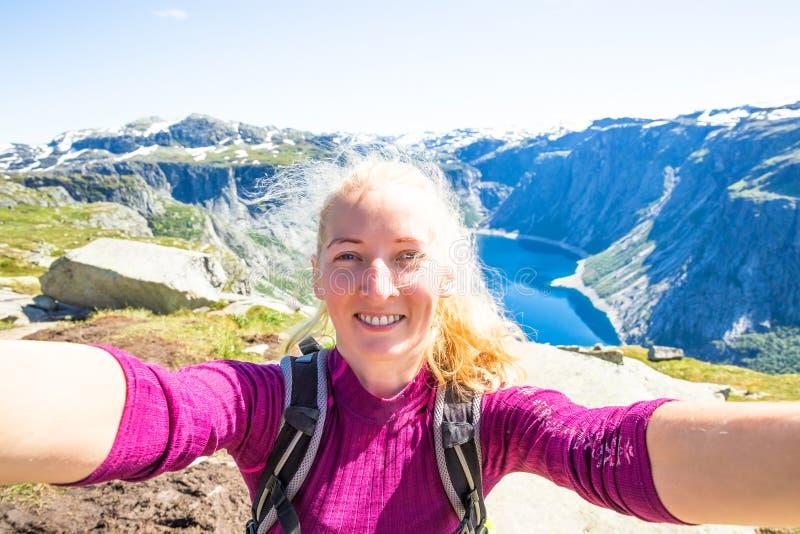 在旅行挪威期间,愉快的人民在峭壁放松 远足路线的Trolltunga 库存照片