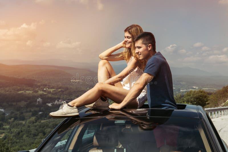 在旅行的年轻夫妇乘汽车一起移动并且享受从上面的自然视图 免版税库存图片