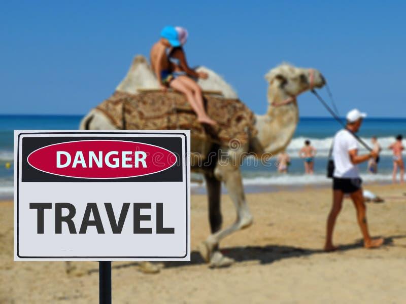 在旅行的标志危险scamers在海滩和骆驼乘坐的孩子 库存图片