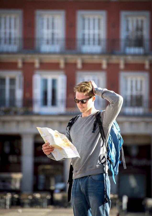 年轻在旅行目的地丢失和混淆的学生背包徒步旅行者旅游看的城市地图 免版税库存照片