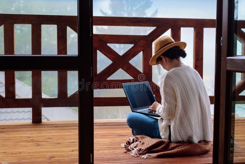 在旅途期间,年轻女人旅客坐在与膝上型计算机的大阳台反对美好的山风景 免版税库存图片