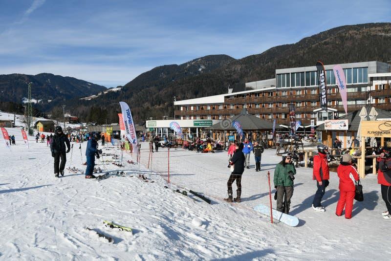 在旅馆前面的滑雪者滑雪滑雪道的在克拉尼斯卡戈拉,斯洛文尼亚 库存图片