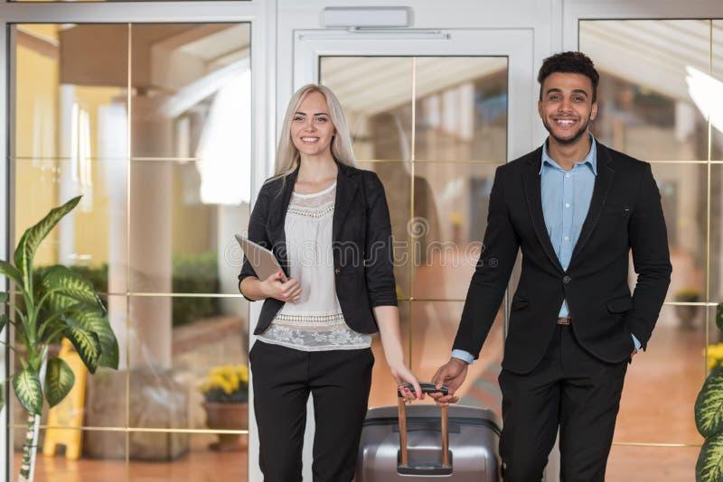 在旅馆大厅、买卖人小组人和妇女客人的微笑的企业夫妇到达 免版税库存照片