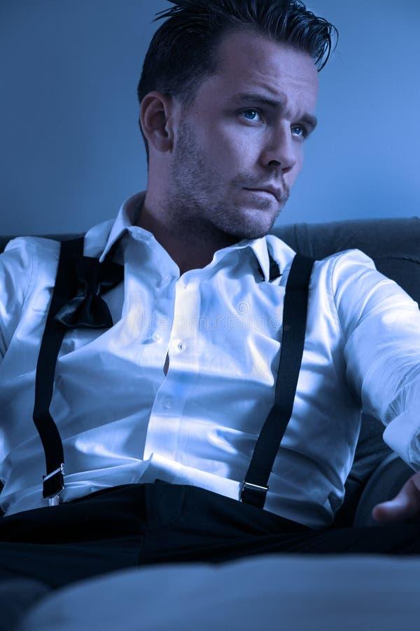 在旅馆客房供以人员佩带的无尾礼服,坐在与宽松领带的椅子 免版税库存图片