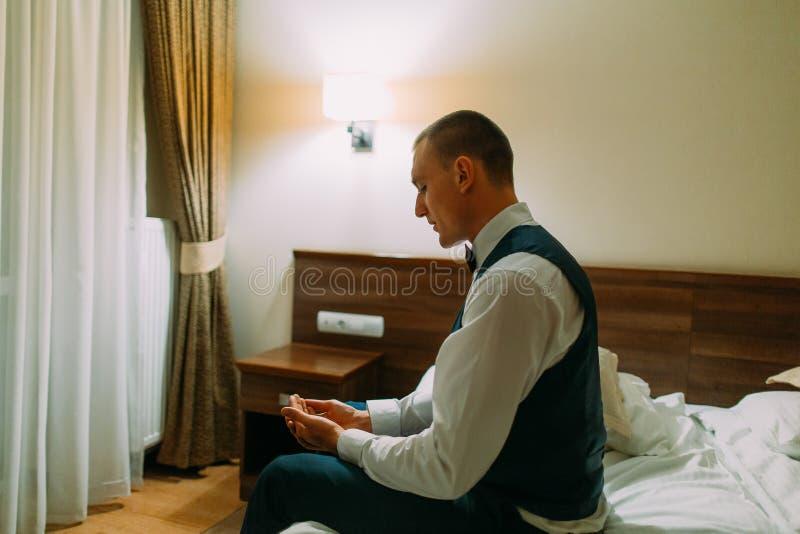 在旅馆客房坐床和看对他的手的年轻运动人 免版税库存图片