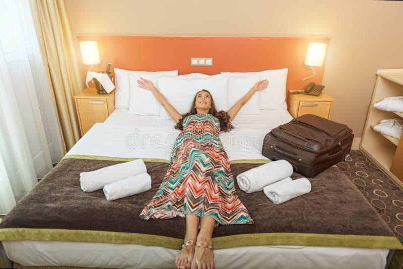 在旅馆客房的床上的少妇 免版税库存照片