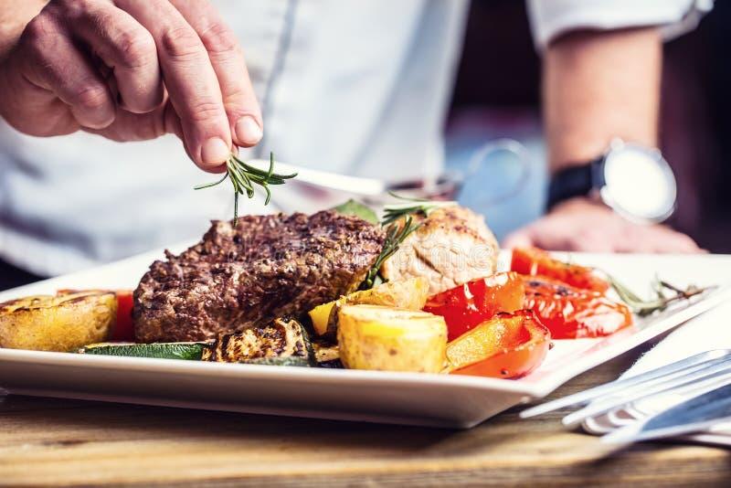 在旅馆或餐馆厨房里烹调仅手的厨师 与菜装饰的准备的牛排 库存图片