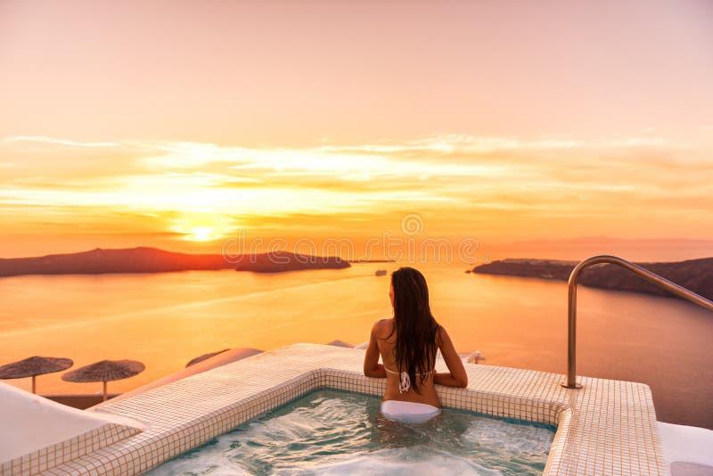 在旅馆极可意浴缸水池观看的日落的豪华旅行圣托里尼假期妇女游泳 欧洲手段目的地假日为 免版税库存图片