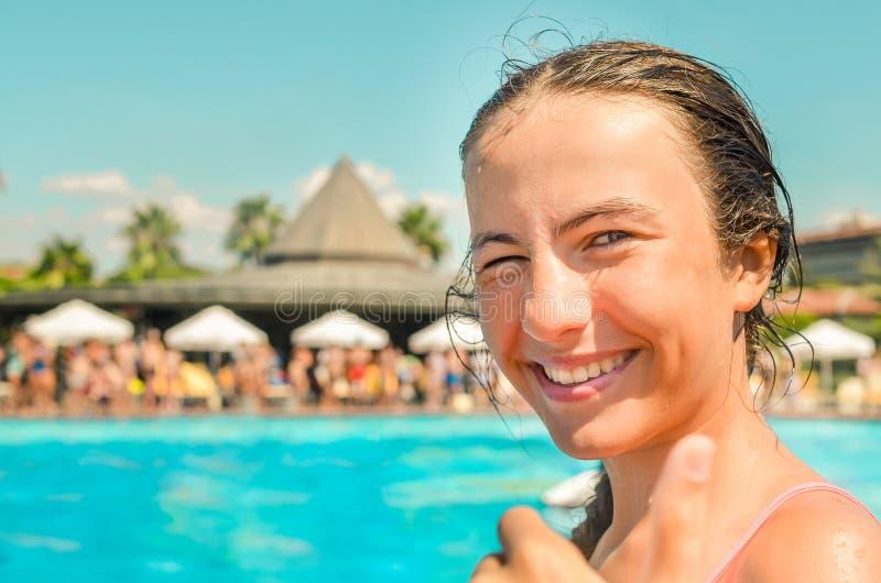 在旅馆水池的微笑的青少年的女孩enjoing的暑假与棕榈和阳伞在背景 库存图片