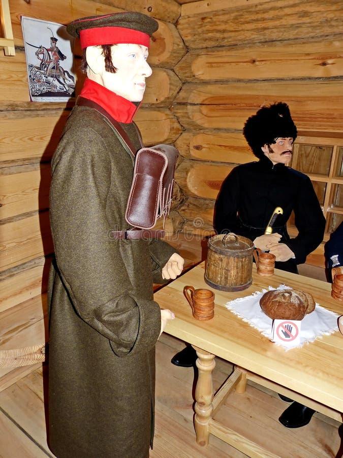 在旅馆 桌等待的食物的传讯者和乌拉尔哥萨克人 免版税图库摄影