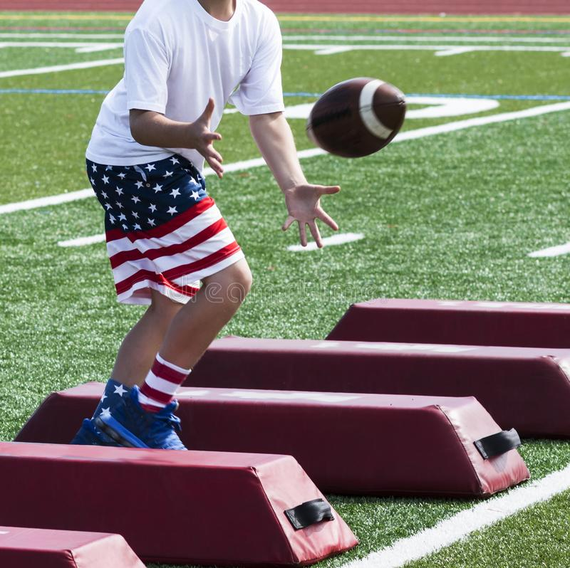 在旗子的足球运动员训练短缺拿到球 免版税图库摄影