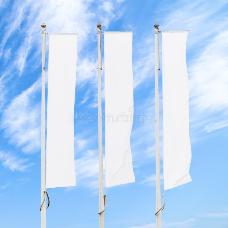 在旗杆的三面空白的白色公司旗子反对多云天空蔚蓝 免版税库存照片