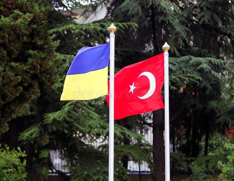在旗杆的土耳其和乌克兰旗子 库存照片