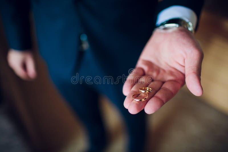 在无尾礼服打扮的一个英俊的愉快的人的画象拿着有定婚戒指的开放箱子 免版税库存图片