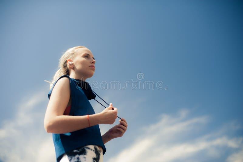 在无线耳机的健身妇女听的音乐,放松在训练以后的运动适合女孩 体育样式蓝牙耳机 图库摄影