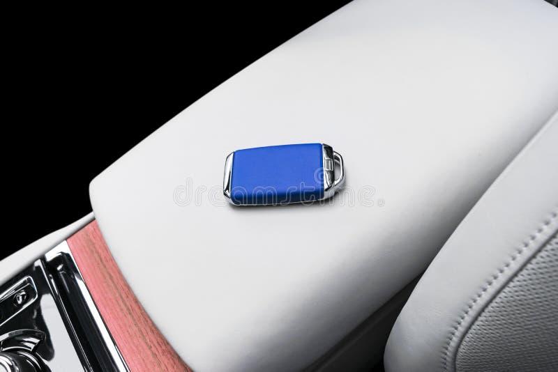 在无线蓝色皮革关键燃烧里面车的特写镜头在自然木盘区的 无线起动引擎钥匙 汽车钥匙遥远的isol 库存图片