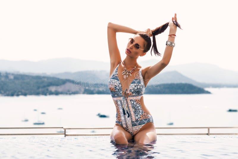 在无限水池的豪华女孩模型 趋向泳装比基尼泳装公寓有日落视图,休闲的被晒黑的运动图和 库存照片