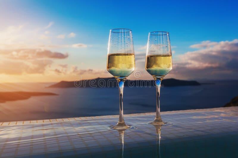 在无限游泳池边缘的两块香槟玻璃在圣托里尼海岛上的日落 免版税图库摄影