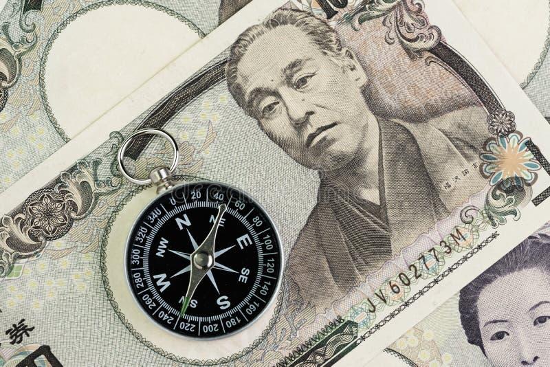 在日元钞票金钱的指南针使用作为日本经济问题解决,财政方向或者钥匙得到成功  免版税库存图片