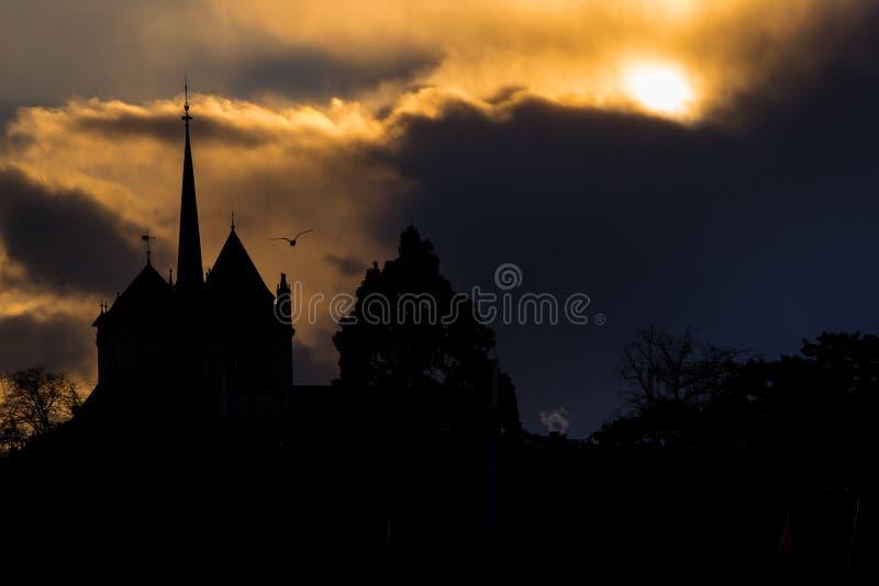 在日内瓦后,瑞士大教堂的太阳设置照亮的动乱的预兆  免版税图库摄影