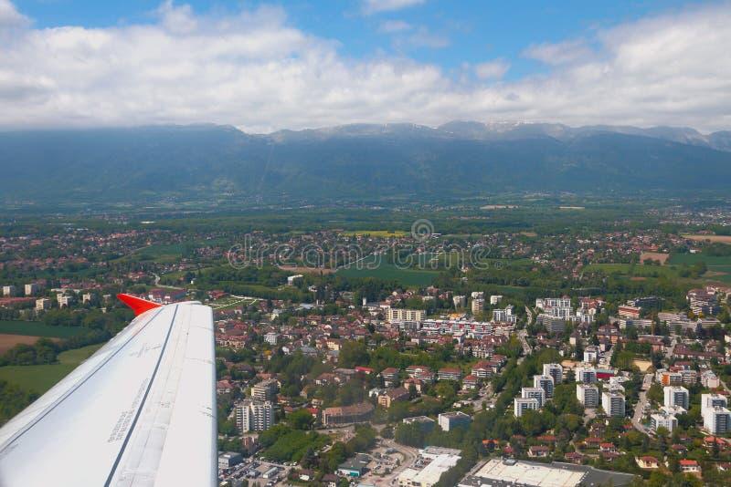 在日内瓦和侏罗纪山附近的平面翼城市下 费尼伏尔泰,法国 免版税库存图片