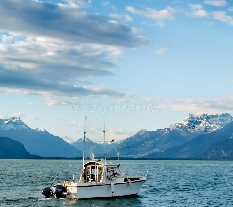 在日内瓦湖凹痕du密地和瑞士阿尔卑斯的风景有作为firstground的一渔船的 免版税库存照片