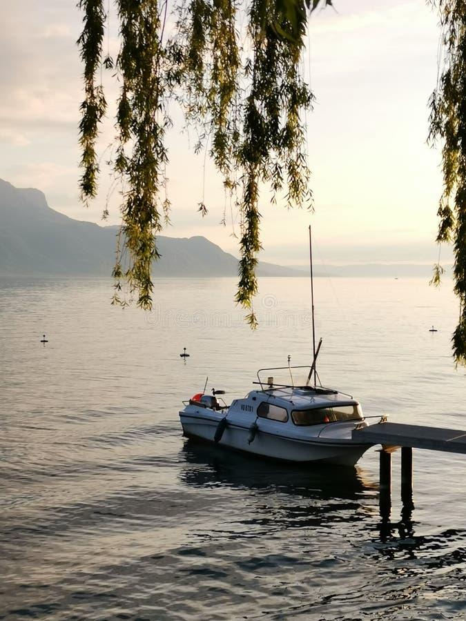在日内瓦湖岸的小船在日落期间的 库存照片