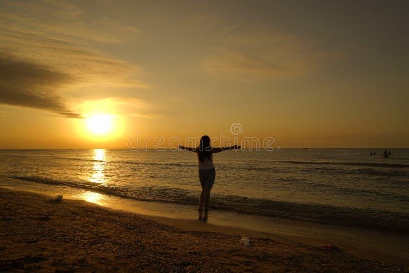 在日出下的妇女开放胳膊在海边 库存照片
