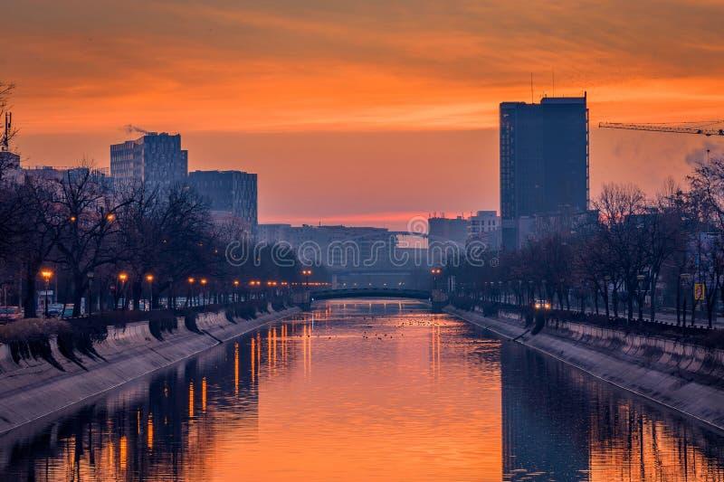 在日出前的充满活力的都市风景射击清早在有一条河的布加勒斯特与鸭子游泳的前景的 库存图片