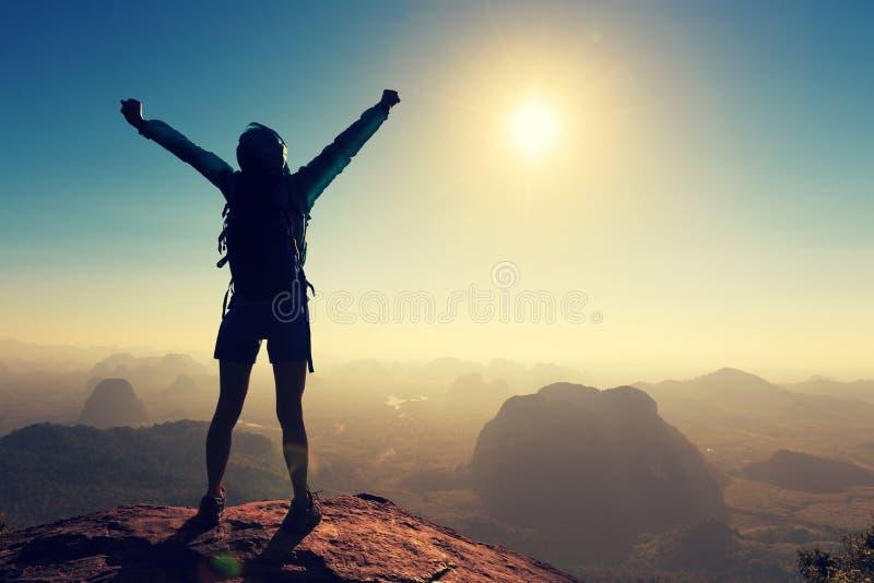在日出山的妇女远足者开放胳膊冠上 免版税库存图片
