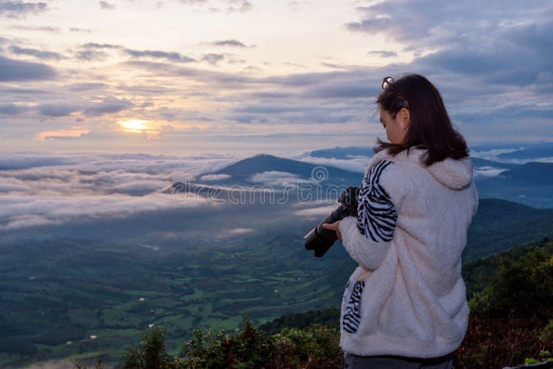 在日出期间,妇女游人看照相机在作为以后在太阳雾和山的自然风景的一张照片 库存图片