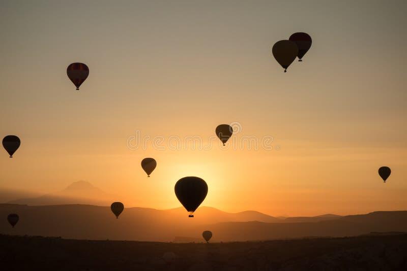 在日出期间,热空气在天空迅速增加 飞行在谷在卡帕多细亚,安纳托利亚,土耳其 火山的山在Goreme n 免版税库存图片