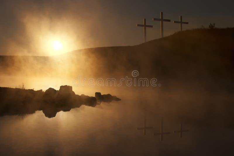在日出的三个十字架在一个有雾的湖复活节早晨 库存图片
