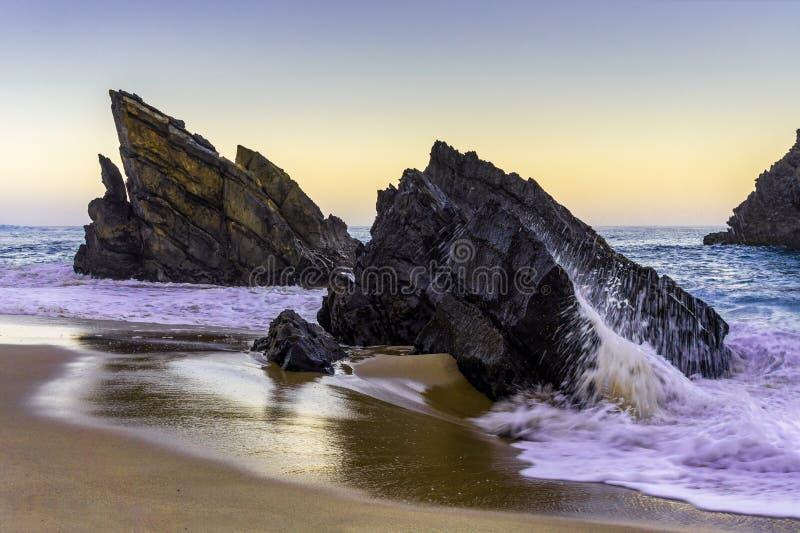 在日出的多岩石的海滩,阿德拉贾,葡萄牙 旅行和企业背景 免版税库存图片