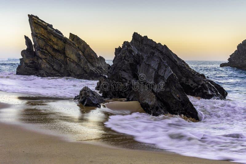 在日出的多岩石的海滩,阿德拉贾,葡萄牙 E 库存图片