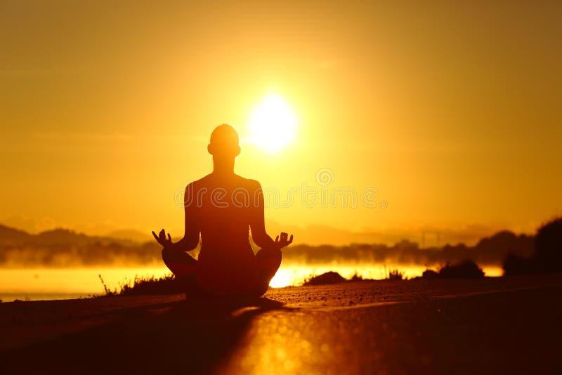 在日出的妇女剪影实践的瑜伽锻炼 免版税库存图片