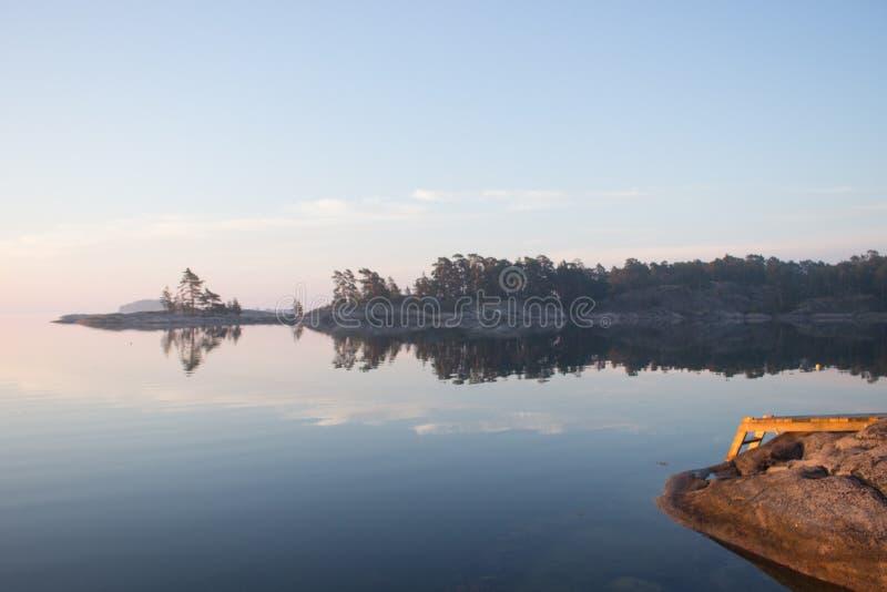 在日出的平安的斯堪的纳维亚海岸线与跳船 免版税库存图片