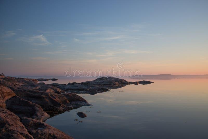 在日出的平安的斯堪的纳维亚海岸线 图库摄影