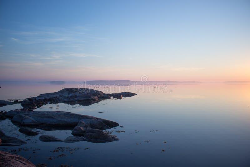 在日出的平安的斯堪的纳维亚海岸线 免版税图库摄影
