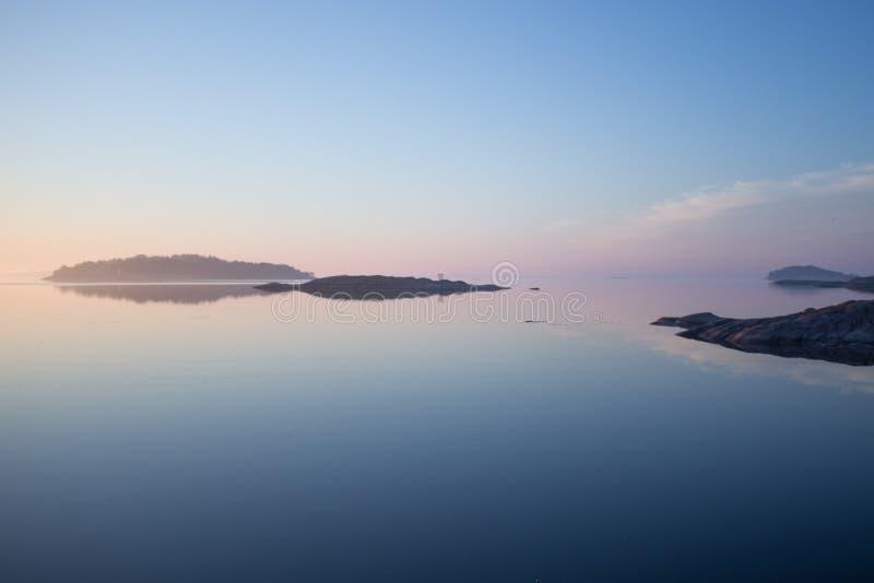 在日出的平安的斯堪的纳维亚海岸线 免版税库存照片