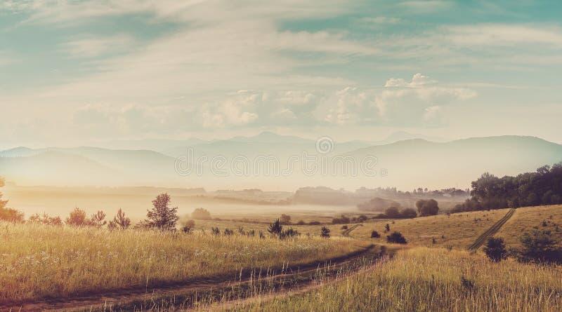 在日出的意想不到的看法 在有雾的农村领域的地面路在山麓小丘 在背景,戏曲的庄严山峰 免版税库存图片