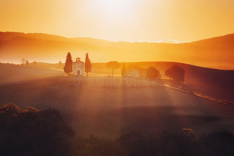 在日出的托斯卡纳风景与玛丹娜二一个小的教堂  免版税库存照片