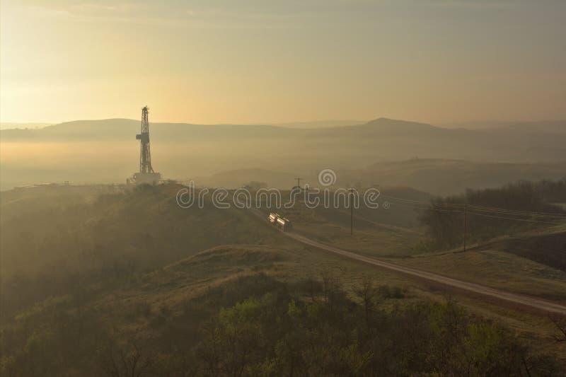 在日出的抽油装置在一个有雾的早晨 免版税库存照片